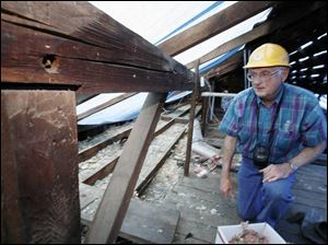 Tony Urbas, a volunteer with Friends of the Lathrop House, checks the attic while the roof is being replaced.