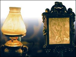 Nineteenth-century German lithophanes mounted in a lamp, left, and a candle shield.
