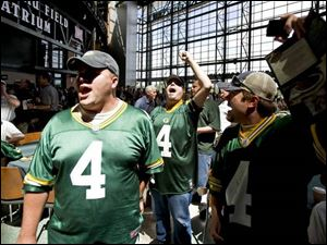 "Shane Keddell, center, of Appleton, Wis., raises his arm and starts a ""bring Brett back"" chant, referring to NFL football quarterback Brett Favre, inside the Lambeau Field Atrium on Thursday, during the annual Green Bay Packers shareholders mee"