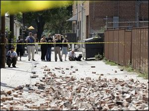 People stand in an alleyway behind police tape near where bricks fell from an unoccupied building during an earthquake Tuesday in Pomona, Calf., near Los Angeles.