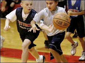 Drew Melick, right, 10, of Sylvania dribbles around Ian Brolley, 10, of Erlanger, Ky., during the Detroit Pistons basketball camp at Owens Community College in Perrysburg Township.