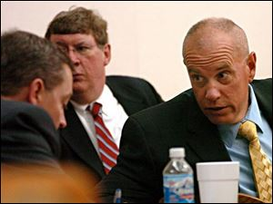 Lima police Sgt. Joe Chavalia, right, talks to his lawyers in a break in his trial in Allen County Common Pleas Court yesterday in the fatal shooting of Tarika Wilson in a drug raid.