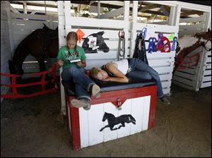 Twins Claire Kaisler, 18, of Tipton and her sister Maria Kaisler take some time to relax with their horse Winston, at the county fair.