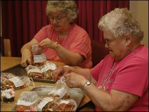 Volunteers Wanda Taylor and Jackie Curtis load up doggie bags of 'nun-better' dog biscuits for sale at the festival. Sacred Heart cooks stir up the toothsome treats just once a year.