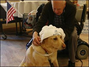 Sacred Heart resident Larry Hartman fits Sam with some headgear a