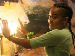Waverly Hill-Mathis demonstrates the heat and light generation of incandescent and fluorescent light bulbs.