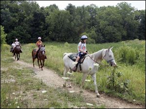 Maggie Jutte, 10, of Bluffton, Ind., at right, enjoys a ride along the 2-mile bridle path at Pokagon State Park in Angola, Ind.