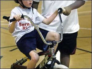 Daniel Rocker works with Jake Emch, 8, of Oregon as he practices on a bicycle with a roller instead of a back wheel. Such camps are planned for 53 U.S. and Canadian cities this year.