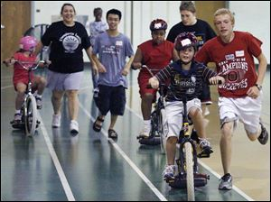 Jonathan Niese, 16, helps Steve Chirgott, 12, in the Lose the Training Wheels camp at the University of Toledo's Health Education Center. The engineer organizing the event used his knowledge of the mathematics of movement.