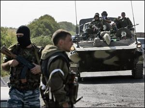 Paramilitary troops secure a Russian military convoy near Gori, Georgia, Wednesday. Russian tanks rolled into the strategic Georgian city of Gori on Wednesday then pressed deeper into Georgia territory, smashing an EU-brokered truce designed to end six-day conflict that has uprooted 100,000 people and scarred the Georgian landscape.