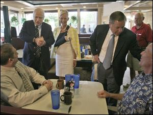 Sen. John McCain, standing with his wife Cindy, center, and Sen. Lindsey Graham (R., S.C.) talk with Steve Boergert, seated left, and Jon Reusch, seated right, during a campaign stop at Kerby's Koney Island diner in Bloomfield Hills, Mich., yesterday. associated pre