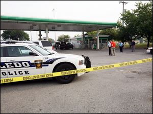 Police tape surrounds the scene at the BP gas station at Dorr Street and Secor Road, where clerk Matthew Dugan was killed.