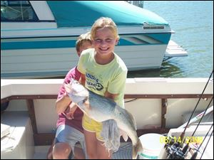 Andrea Cromley, 9, of Bowling Green, with a little help from her brother, Mitch, shows off a 29-inch walleye she landed.