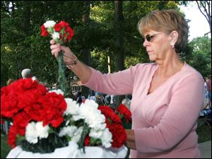 Pam Rettig of Findlay gathers flowers to give out to people to save or throw into the adjacent Blanchard River as part of the one-year commemoration of the August, 2007, flood.