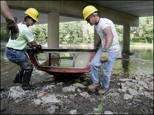 Findlay residents Brian Bibler, left, and Eric Stroub work for the National Emergency Grant Project clearing debris from the Blanchard River in Findlay.