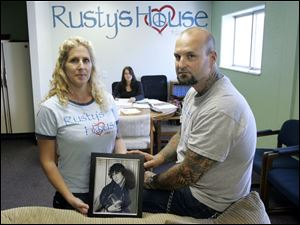 Amy and Rick Marvin, with a portrait of their son, Rusty, with their daughter, Hailey Marvin, seated behind them, at Rusty s House. Mr. and Mrs. Marvin established the nonprofit center offering help to those with addictions after Rusty s death.