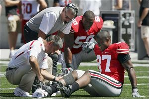 Coach Jim Tressel, left, and a team doctor examine Lawrence Wilson s leg in Ohio State s opener against Youngstown State  last year.