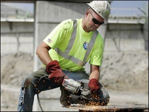 Jody Holly, of Walter Toebe Construction Co. of Wixom, Mich., grinds base mats for support towers at the construction site.