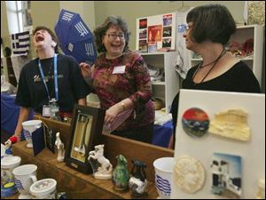 Boutique vendors Kathy Andros, left, Soteria Houlles, and Maria Papps of Sylvania share a laugh at their booth durin
