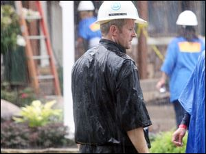 Mr. Schlachter works through rain at the Extreme Makeover site.
