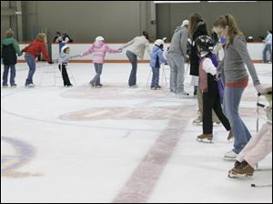 Jamie Frazee, right, in skating chair, is helped around the ice by volunteers during rehearsal for Gliding Stars Adaptive Ice Skating at the University of Findlay's Clauss Ice Arena.