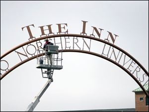 A worker puts the finishing touches on the sign for the college's new 75-room hotel.
