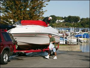 Don Pelchat of Holland unties his boat and prepares to tow it from the Rossford Marina with some assistance from Joe Jarvis of Perrysburg.