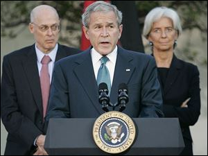 President Bush pauses during a press conference with the G7 Finance Ministers in the Rose Garden of the White House Saturday, Oct. 11, 2008, in Washington. At back left is Treasury Secretary Henry Paulson and French Finance Minister Christine Lagarde, right.
