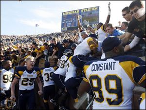 University of Toledo players climb into the stands at Michigan Stadium yesterday to celebrate with Rocket fans after the team's victory over Michigan. 