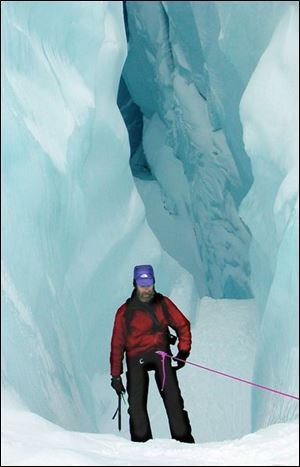 Konrad Steffen descends into an icy crevice known as a 'moulin' on the Petermann glacier in northwestern Greenland.
