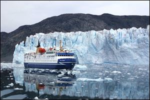 A cruise ship passes by the foot of Greenland s Eqi Glacier, one of the world s most active for calving icebergs. Greenland and its ice sheets are immense. The island spans 1,660 miles from north to south.