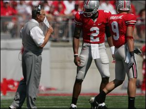 OSU coach Jim Tressel gives instructions for the next play to Terrelle Pryor (2) and Brian Hartline to take into the huddle. (THE BLADE/LORI KING)