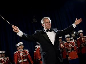 "President Bush turns to the audience after conducting the United States Marine Corps Band, known as ""The President's Own,"" during the annual dinner of the White House Correspondents' Association in April."