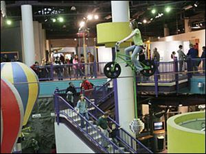 Isabella Frownfelter, 11, of Flint, Mich., takes the high-wire bicycle for a whirl during COSI s last day of operation in December, 2007. The downtown science museum has remained closed.