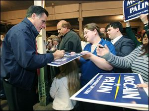 Former presidenital hopeful Mitt Romney signs autographs during an appearance Sunday night in Toledo.