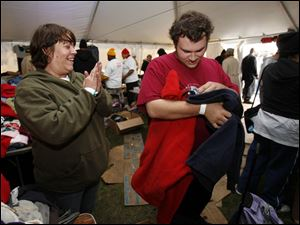 Tent City Mayor Michele Ross helps Jason Jock find a sweatshirt in his size during the three-day event on the Civic Center Mall.