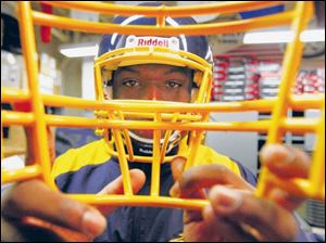 University of Toledo football player Tyson Patrick, Jr., chooses a face mask after he is issued a new helmet.