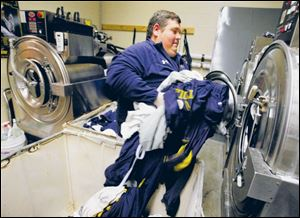 UT Football equipment manager Rusty Rogers does a load of laundry as part of preparations for the next day s practice.