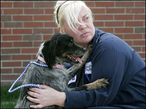 Jodi Duff, an employee of the Lucas County Dog Warden, holds a mixed 2-year-old female dog that's available for adoption. They were at a news conference where county government officials and local animal groups pledged to work together in an effort to increase the rate of adoptions from the county's dog pound by 10 percent next year. Skeldon