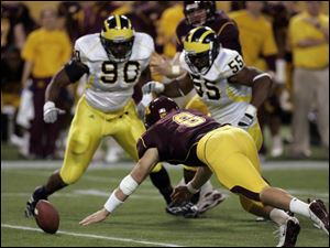 Minnesota quarterback Adam Weber dives to recover a fumble as he beat Michigan's Tim Jamison (90) and Brandon Graham (55) to the loose ball in the second quarter Saturday.