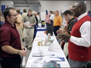 Cameron Volkman, left, of Delta discusses job opportunities with Bobby Green of Western & Southern Financial Group.