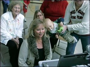 Matthew Heller's family, above, from left, grandmother Opal Wagner; his mother, Dana Heller; his baby nephew, Jaxon Brenton, 9 months, and sister Jessica Brenton communicate with Mr. Heller in Morocco through an Internet Web camera.