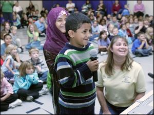 Lozah Alomari, 8, and her brother, Mohamed Alomari, originally from Yemen, ask questions through a video link with Matthew Heller, a Monroe man who is a Peace Corps volunteer in Morocco. Their teacher, Angela Sneider, watches the exchange.