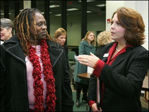 Toledo photographer Audrey Johnson, left, speaks with Julie Henahan, executive director of the Ohio Arts Council, after a public forum the state council held at the Sanger branch of the Toledo-
