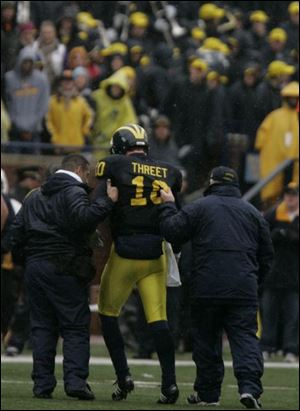 Michigan s Steven Threet is helped from the field after sustaining head and knee injuries during the second half.