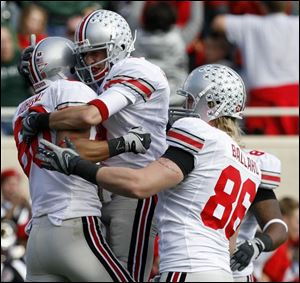 Brian Robiskie, left, is congratulated by Brian Hartline, center, and Jake Ballard after catching a TD pass for OSU. A win over Michigan would give OSU a share of the Big Ten title.