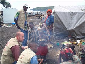 Luke King, left, consults with residents of a displacement camp in the conflict-ridden Democratic Republic of Congo.