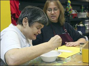 Karen Lewis, in foreground, works with adult service provider Tammy Wood on making a glitter Christmas ornament in the 'Kan Du Studio' at the Blanchard Valley Center. The agency has regained its accreditation from the Ohio Department of Mental Retardation and Developmental Disabilities after losing it in 2007.