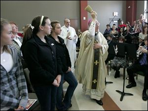 Bishop Leonard Blair blesses the Blessed John XXIII Parish Life Center on Dixie Highway in Perrysburg as, from left, Alexa Long, Stephanie Richards, and Hailey Oeder, all 14, watch.