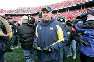 Michigan coach Rich Rodriguez walks off the field after losing the final game to Ohio State to finish the season 3-9.